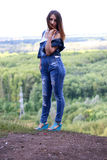 Attraktiv kvinna som poserar mot bakgrunden av skogen Royaltyfri Fotografi