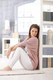 Attraktiv kvinna som poserar vid bokhyllan Royaltyfri Fotografi
