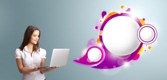 Attraktiv kvinna som rymmer en bärbar dator och framlägger abstrakt anförande Arkivfoto