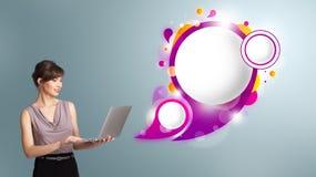 Attraktiv kvinna som rymmer en bärbar dator och framlägger abstrakt anförande Arkivbilder