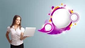 Attraktiv kvinna som rymmer en bärbar dator och framlägger abstrakt anförande Royaltyfria Foton