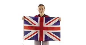 Attraktiv kvinna som rymmer en engelsk flagga på vit bakgrund arkivfilmer