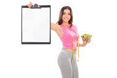 Attraktiv kvinna som rymmer en sallad och en skrivplatta Arkivbild