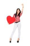 Attraktiv kvinna som rymmer en stor röd hjärta Royaltyfri Bild