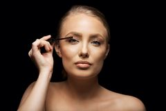 Attraktiv kvinna som sätter mascara på hennes ögonfrans Arkivbild