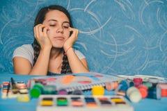 Attraktiv kvinna som söker för musa med målarfärger Arkivfoto