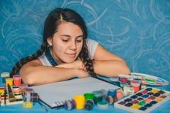 Attraktiv kvinna som söker för musa med målarfärger Arkivfoton