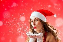 Attraktiv kvinna som Santa Claus slående snow Arkivbild