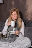 Attraktiv kvinna som ser hennes varma drink i koppen Royaltyfri Foto