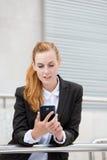 Attraktiv kvinna som ser Smartphone Arkivfoton