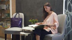 Attraktiv kvinna som sitter i semesterortkorridor och läsebok stock video