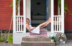 Attraktiv kvinna som sitter på en veranda Fotografering för Bildbyråer