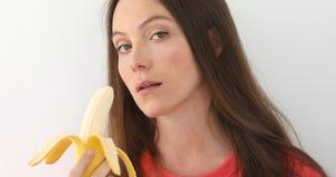 Attraktiv kvinna som skalar och äter en stor banan Royaltyfri Fotografi
