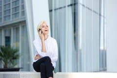 Attraktiv kvinna som skrattar med mobiltelefonen Arkivbild