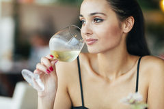 Attraktiv kvinna som smakar vitt vin Arkivbilder
