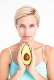 Attraktiv kvinna som visar halva av en avokado arkivfoto