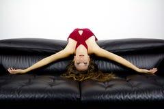 Attraktiv kvinnabenägenhet mot en svart soffa Arkivfoton