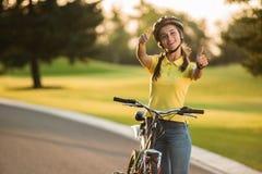 Attraktiv kvinnacyklist som ger upp två tummar Royaltyfria Foton