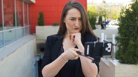 Attraktiv kvinnadanande vänder mot och ta fotoet av henne med smartphonen genom att använda selfiepinnen arkivfilmer