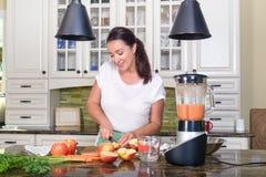 Attraktiv kvinnadanandesmoothie i blandare i modernt kök Royaltyfri Bild