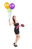 Attraktiv kvinnaholdingballonger och gåva Royaltyfria Bilder