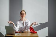Attraktiv kvinnameditation på tabellen med koppen och bärbara datorn arkivbild