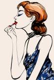 Attraktiv kvinnamodemodell som applicerar läppstift Arkivbild