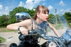 Attraktiv kvinnaritt en svart motorbike Royaltyfri Bild
