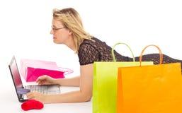 Attraktiv kvinnashopping över internet Arkivfoto