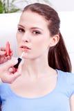 Kvinna som applicerar läppstift på naturlig skönhet för kanter Arkivfoto