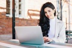 Attraktiv kvinnlig blogger som skriver den nya utmanande stolpen genom att använda funktionsläge arkivbilder