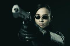 Attraktiv kvinnlig brottsling som pekar ett vapen arkivfoton