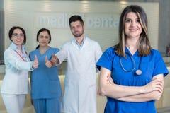 Attraktiv kvinnlig doktor framme av den medicinska gruppen Arkivfoton