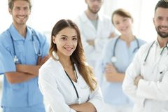 Attraktiv kvinnlig doktor med den medicinska stetoskopet som är främst av den medicinska gruppen Arkivbilder