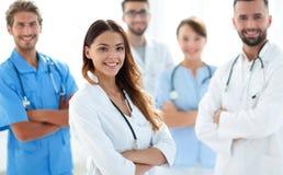 Attraktiv kvinnlig doktor med den medicinska stetoskopet som är främst av den medicinska gruppen Arkivbild