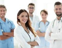 Attraktiv kvinnlig doktor med den medicinska stetoskopet som är främst av den medicinska gruppen Royaltyfri Fotografi