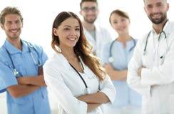 Attraktiv kvinnlig doktor med den medicinska stetoskopet som är främst av den medicinska gruppen Royaltyfri Bild