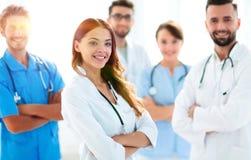 Attraktiv kvinnlig doktor med den medicinska stetoskopet som är främst av den medicinska gruppen Royaltyfria Foton