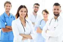 Attraktiv kvinnlig doktor med den medicinska stetoskopet som är främst av den medicinska gruppen Arkivfoton