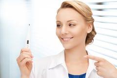 Attraktiv kvinnlig doktor med termometern Arkivbild