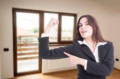 Attraktiv kvinnlig fastighetsmäklare som visar hennes muskel Fotografering för Bildbyråer