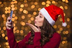 Attraktiv kvinnlig i den santa hatten genom att använda smartphonen och överföra kyssen Royaltyfri Bild
