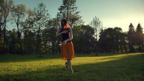 Attraktiv kvinnlig i lång röda den kjolbanhoppning och dansen som är utomhus- i en parkera stock video