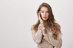 Attraktiv kvinnlig kvinna med härligt långt håranseende i den trendiga aftonklänningen, tryckande på framsida slappt som om på royaltyfria bilder