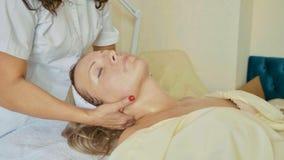 Attraktiv kvinnlig på den vård- klubban för brunnsort som får ett ansikts- tillvägagångssätt och massage Royaltyfria Bilder