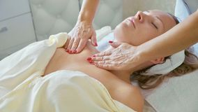 Attraktiv kvinnlig på den vård- klubban för brunnsort som får ett ansikts- tillvägagångssätt och massage Royaltyfri Foto
