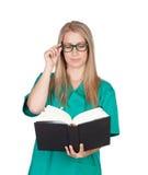 Attraktiv läkarundersökning med exponeringsglas som läser en bok Fotografering för Bildbyråer