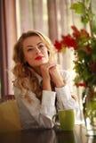 Attraktiv läsebok för ung kvinna, medan dricka kaffe Arkivbild