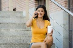 Attraktiv latinsk kvinna i hennes lyckliga tjugotal tala hennes smarta telefon för mobil royaltyfria foton