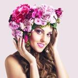 Attraktiv le härlig flicka med blommakronan fotografering för bildbyråer